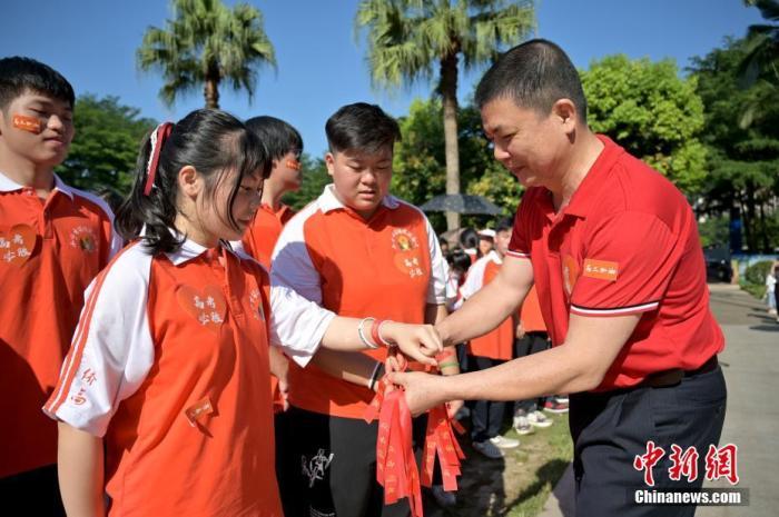 资料图:广西华侨实验高中的教师为高三学子系上红丝带,盼望学子高考必胜。俞靖摄