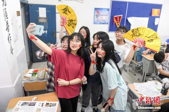 资料图:6月6日,2021年高考前夕,湖南长沙同升湖实验学校高三年级,考生们在教室内合影。杨华峰摄