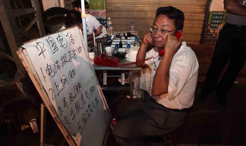 8月4日,一名災區群眾在巧家縣包谷垴鄉的電信服務網點撥打電話報平安。