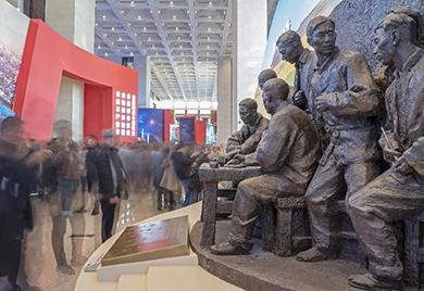 """观众在观看安徽小岗村农民按下包产到户""""红手印""""的雕塑"""