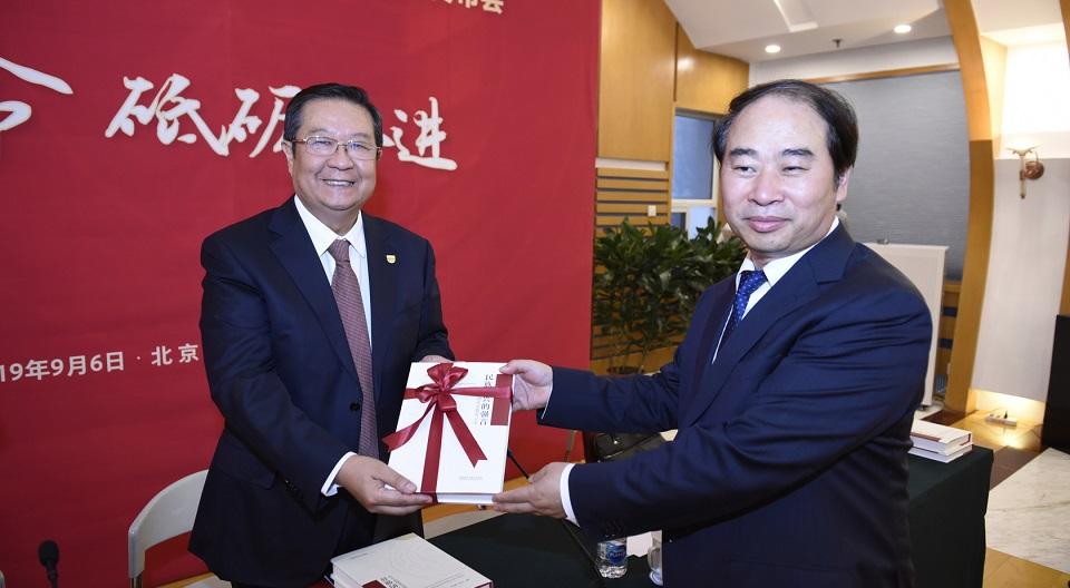 本书主编王定华向教育部原副部长、中国教育国际交流协会会长刘利民赠书