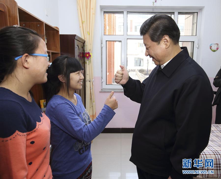 """在呼和浩特市儿童福利院,习近平鼓励聋哑女孩王雅妮和放假""""回家""""的大学生闫志净好好学习,学业有成。他伸出大拇指向她们学习哑语。"""