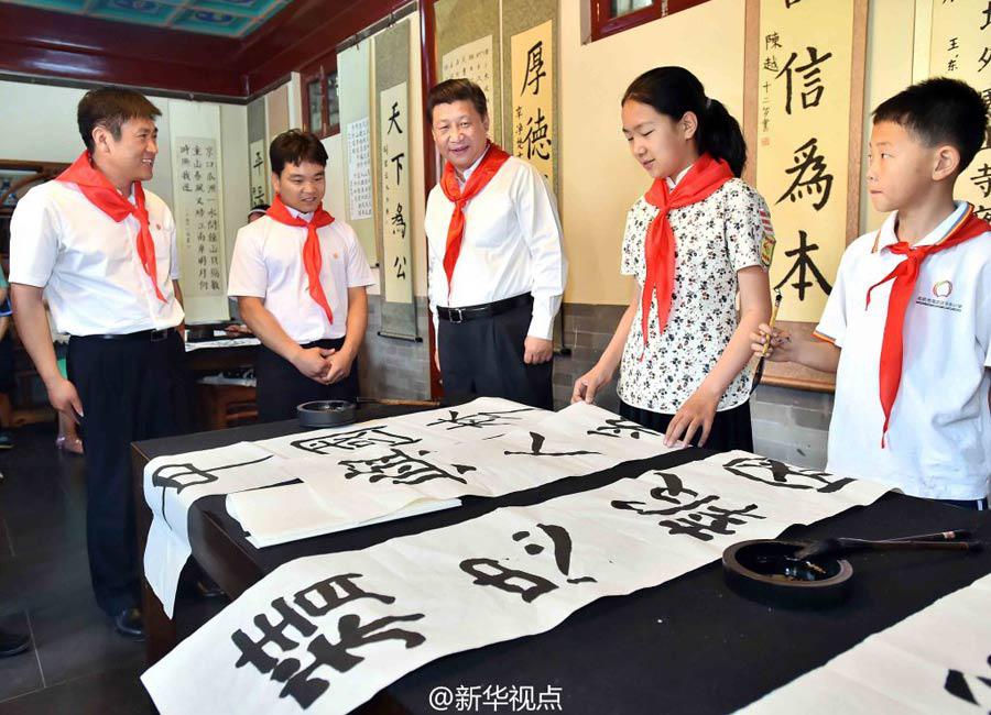 """在北京市海淀区民族小学,看到孩子们写的""""精忠报国"""",习近平说:""""我从小就受这4个字影响,四五岁时妈妈买了小人书,给我讲'精忠报国、岳母刺字'的故事......精忠报国,是我一生的目标。"""""""