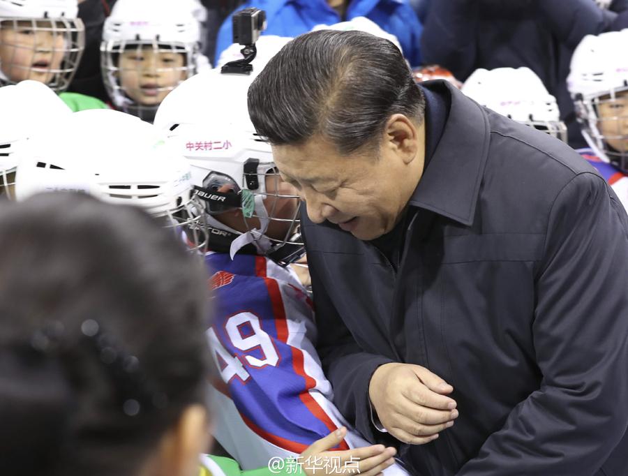 """在北京五棵松体育中心,习近平拉着一位小冰球队员的手,俯下身,与他肩碰肩,做了一个""""对抗""""的姿势,笑着说,小伙子块头要再长大一点。"""