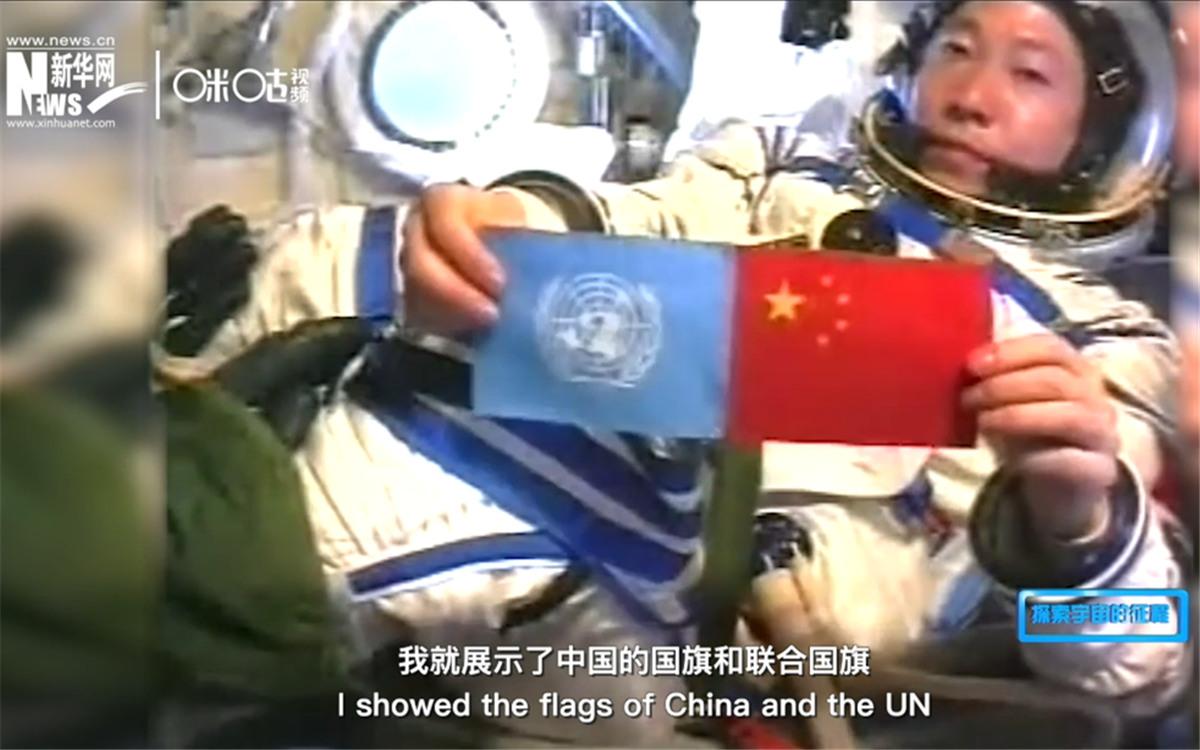 中国首位航天员杨利伟展示中国国旗和联合国旗