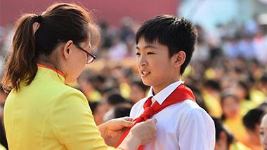 辅导老师在广场上为学生整理着装