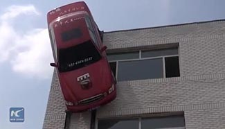Man hangs car on facade of three-story building