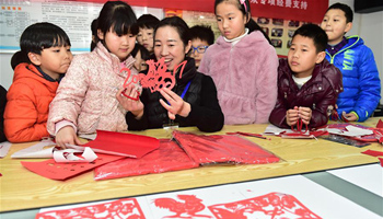 Teacher introduces skills of window paper-cutting to children in E China