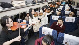 Students play violin on high-speed train