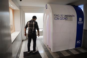 People pass ozone-based sanitation tunnel in Mexico City