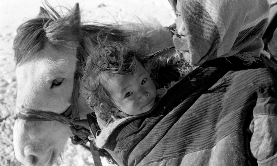 1990年3月,西藏当雄县纳木湖乡三村女牧民斯卓不畏严寒,怀抱幼子,准备到远处放牧。澳门金沙国际娱乐社记者觉果摄