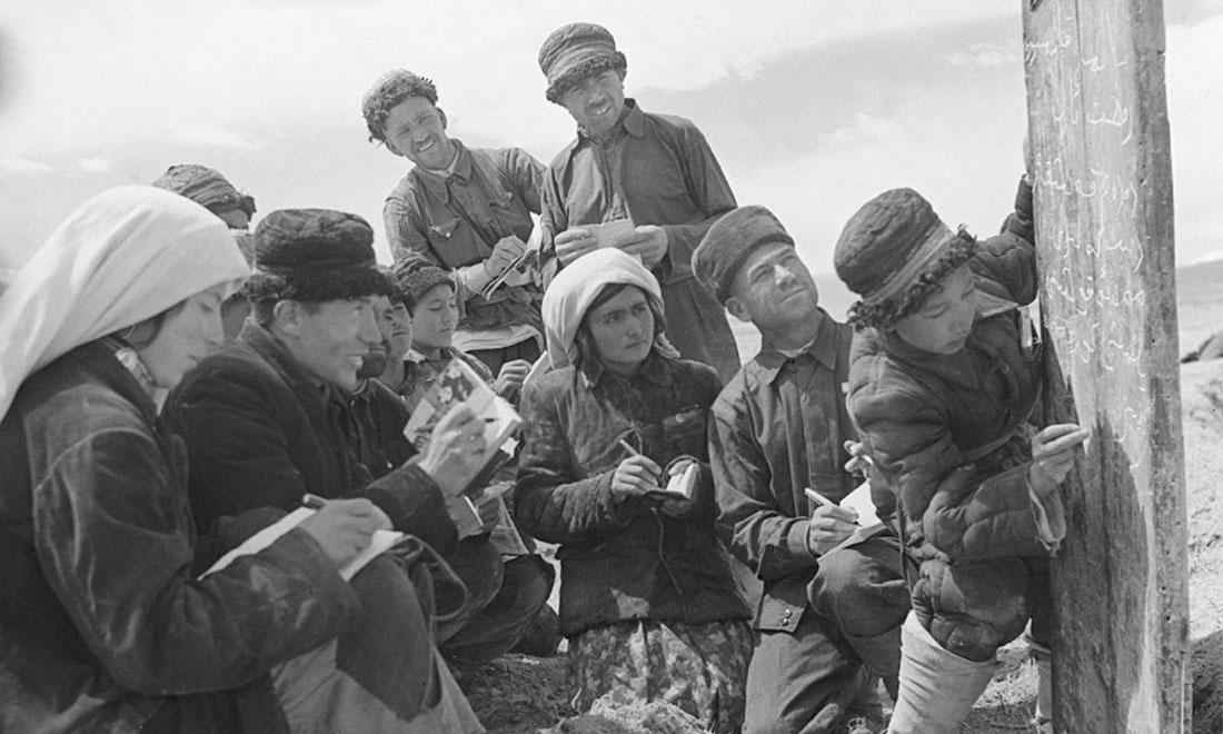1960年6月,新疆慕士塔格峰下,大人們在小學生幫助下學習文化。新華社記者武純展攝