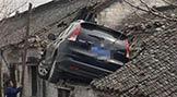 額滴個神!為避讓三輪 轎車飛上三米高屋頂!