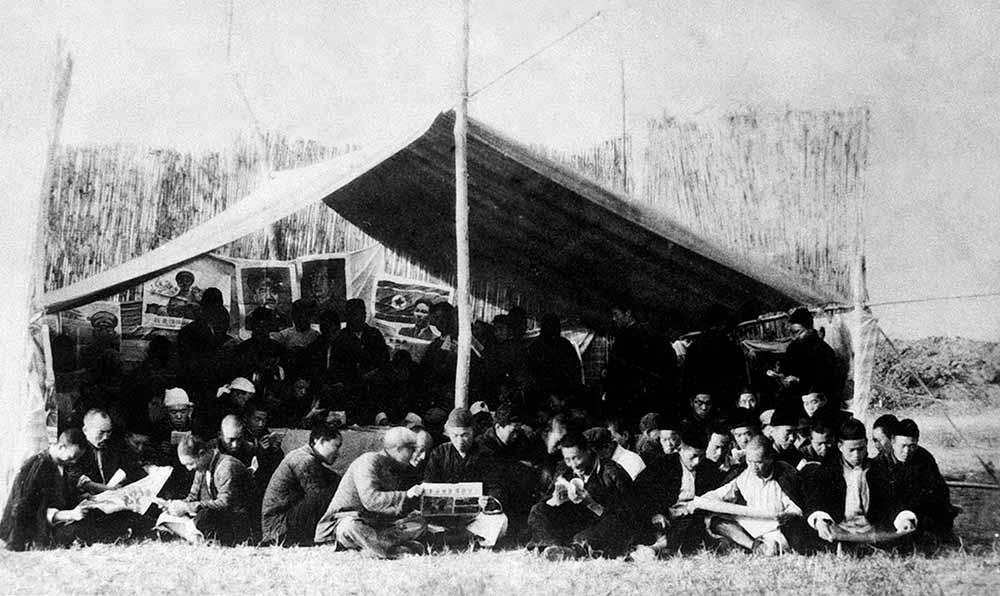 河南許昌專區民工在治淮工地上的讀書棚前閱讀。