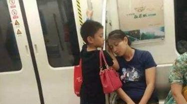 暖!男孩地鐵裏用手為媽媽墊著睡覺