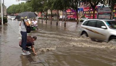道路積水六旬大爺手挖下水口 路人為其撐傘