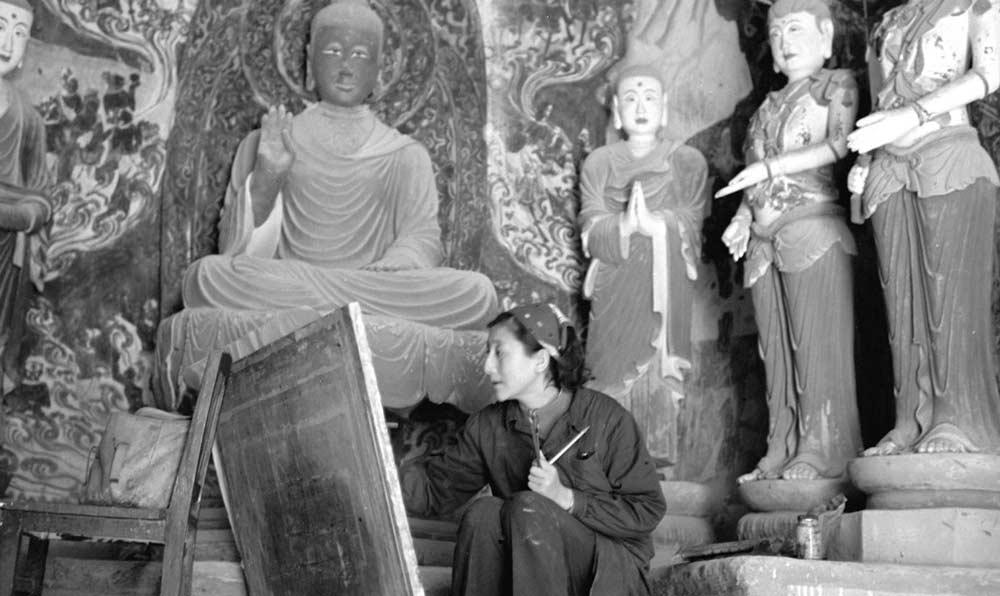 來自新疆的美術工作者在敦煌莫高窟臨摹佛像和壁畫。