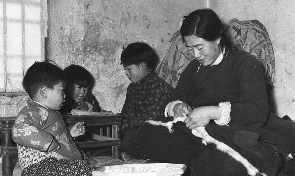 河北省蠡縣新興鄉新新農業生産合作社社員董桂芝正在給孩子做新棉衣。