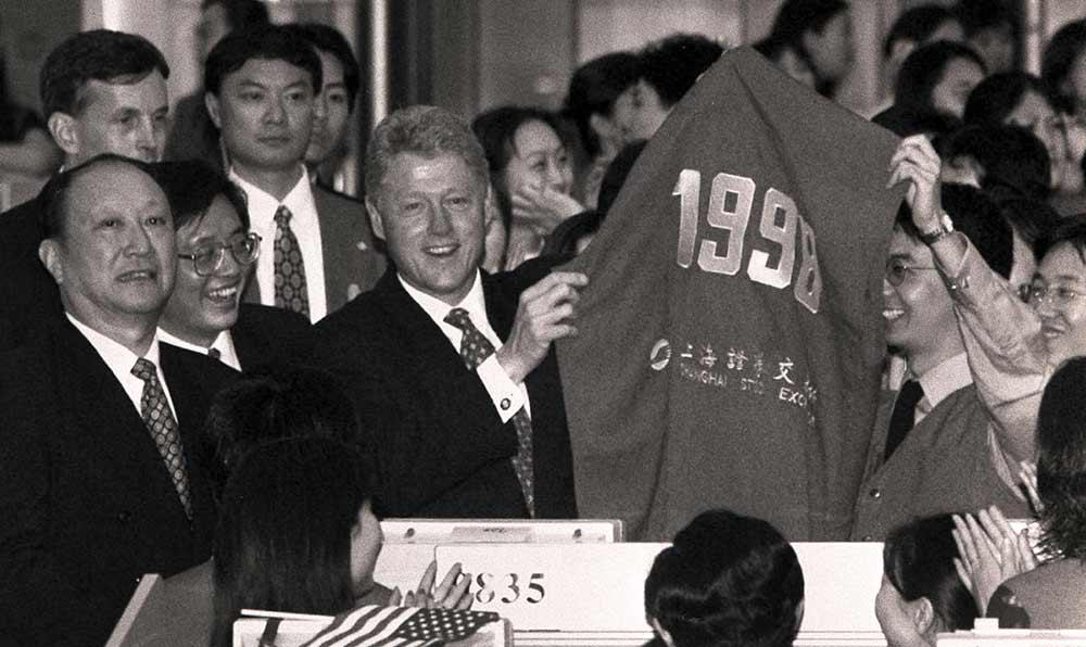 """上海證券交易所人員向克林頓贈送編號為""""1998""""的紅馬甲。"""