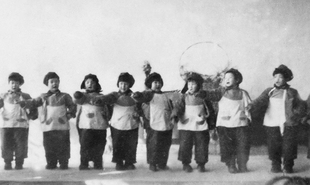 1950年,軍委直屬機關保育院的孩子們在工作人員自己修建的禮堂內表演節目。