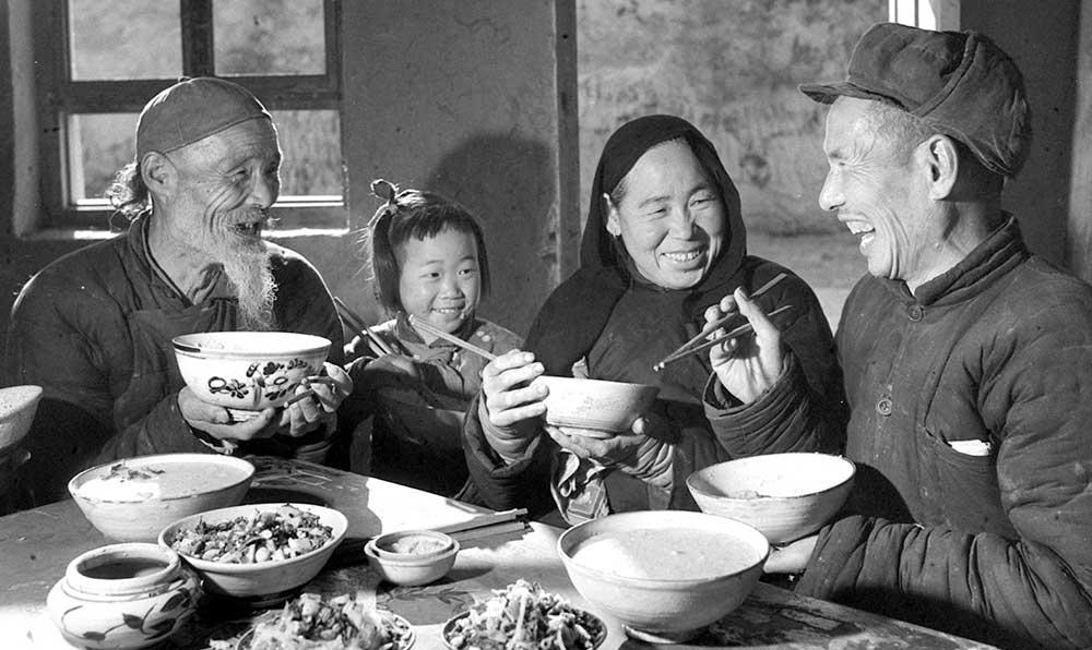 雷永珍(右)在食堂裏和社員同桌吃飯,徵求社員對改進夥食的意見。