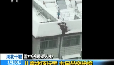 湖北十堰:雪中送暖暖人心兒童樓頂玩雪 市民帶離險境