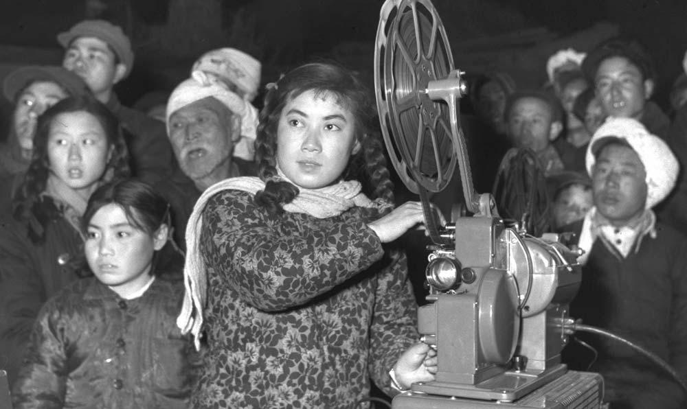 山西省平遙縣第二電影放映隊的隊長陳秀蓮(前者)在為農民放映電影。