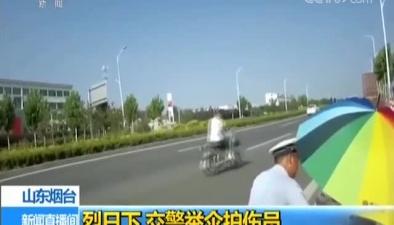 山東煙臺:烈日下 交警舉傘護傷員