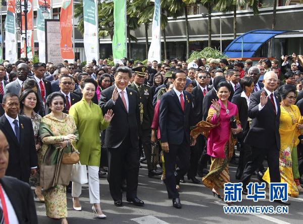 這是習近平和夫人彭麗媛同印度尼西亞總統佐科夫婦等走在隊伍前列,一邊走一邊向道路兩旁的人群揮手致意。新華社記者 蘭紅光 攝