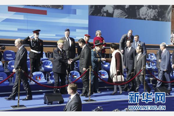 習近平和夫人彭麗媛在檢閱臺上同老戰士親切握手。新華社記者 鞠鵬 攝