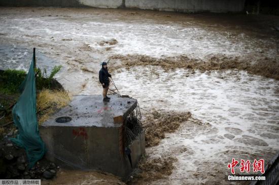 圣地亚哥民众看着河中奔腾的洪水。