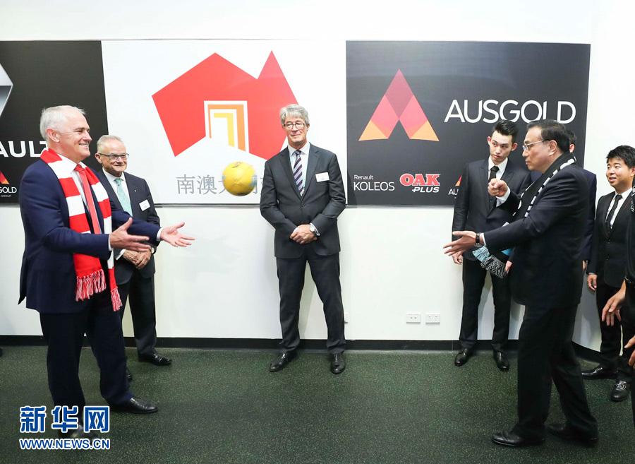 當地時間3月25日,國務院總理李克強在悉尼與澳大利亞總理特恩布爾共同觀看澳式足球比賽。這是李克強和特恩布爾興致勃勃地練習起澳式足球的傳接球動作。新華社記者 龐興雷 攝