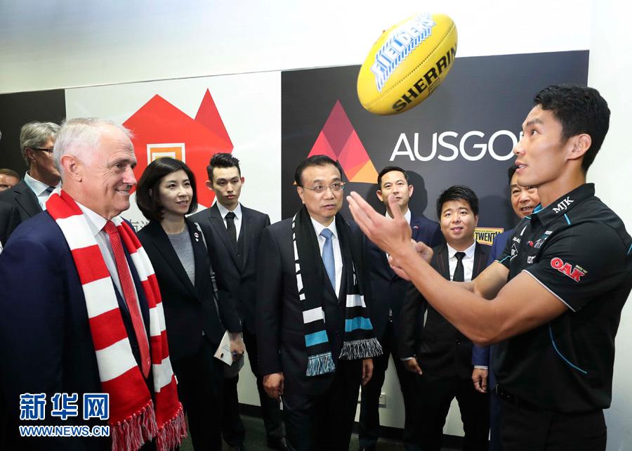 當地時間3月25日,國務院總理李克強在悉尼與澳大利亞總理特恩布爾共同觀看澳式足球比賽。這是李克強和特恩布爾共同來到熱身區同球員親切交流互動。新華社記者 龐興雷 攝