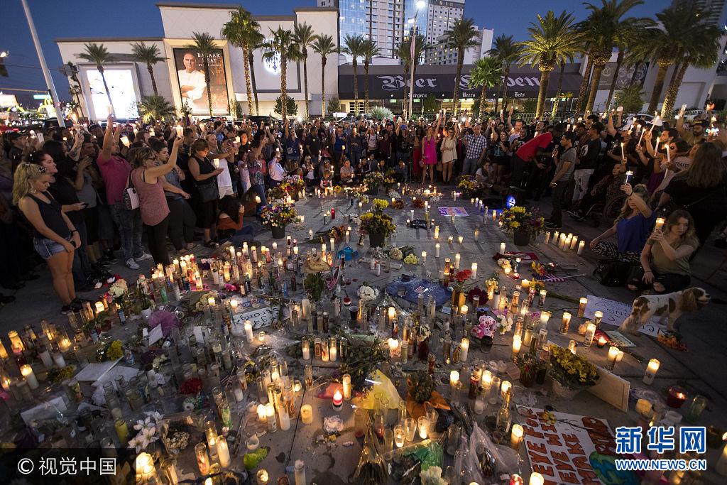 當地時間2017年10月8日,美國拉斯維加斯,民眾參加燭光守夜,紀念拉斯維加斯槍擊案發生一周。***_***LAS VEGAS, NV - OCTOBER 8: Mourners hold their candles in the air during a moment of silence during a vigil to mark one week since the mass shooting at the Route 91 Harvest country music festival, on the corner of Sahara Avenue and Las Vegas Boulevard at the north end of the Las Vegas Strip, on October 8, 2017 in Las Vegas, Nevada. On October 1, Stephen Paddock killed 58 people and injured more than 450 after he opened fire on a large crowd at the Route 91 Harvest country music festival. The massacre is one of the deadliest mass shooting events in U.S. history. (Photo by Drew Angerer/Getty Images)