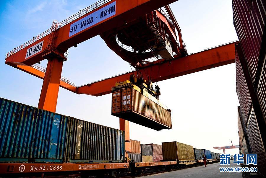 在青岛胶州湾国际物流园,龙门塔吊在往中亚班列上装载货物(2019-08-18摄)。该班列将通过阿拉山口至哈萨克斯坦的阿拉木图。新华社记者 郭绪雷